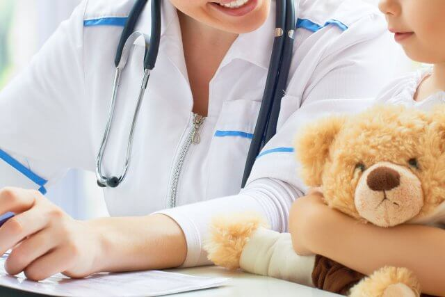 doctor with little girl holding teddy bear