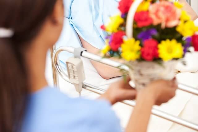 nurse bringing flowers to patient