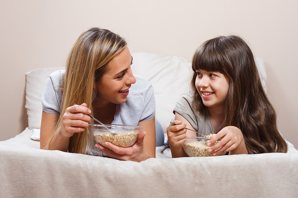 Beautiful mother and daughter are talking while having a breakfast in bed.
