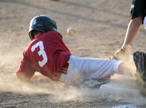 youth league boy baseball player sliding into third base. Dust and dirt flying. Slightly blurred for sense of motion