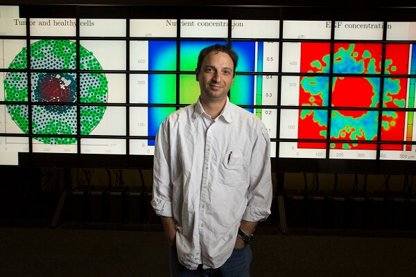 A photo od Dr. Yankeelov standing in front of cancer cell displays.