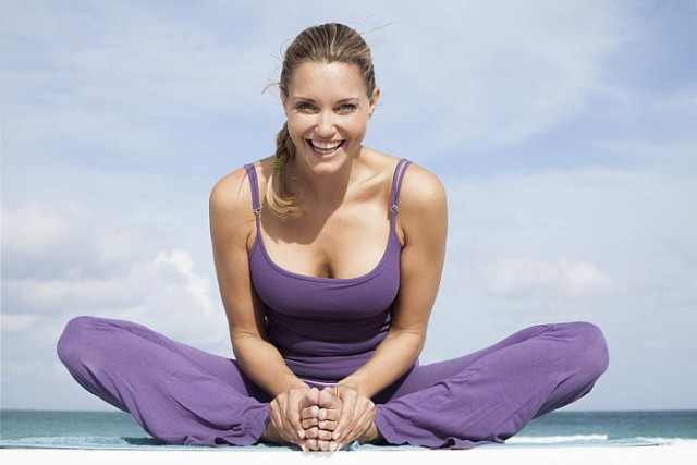 happy woman doing yoga at beach