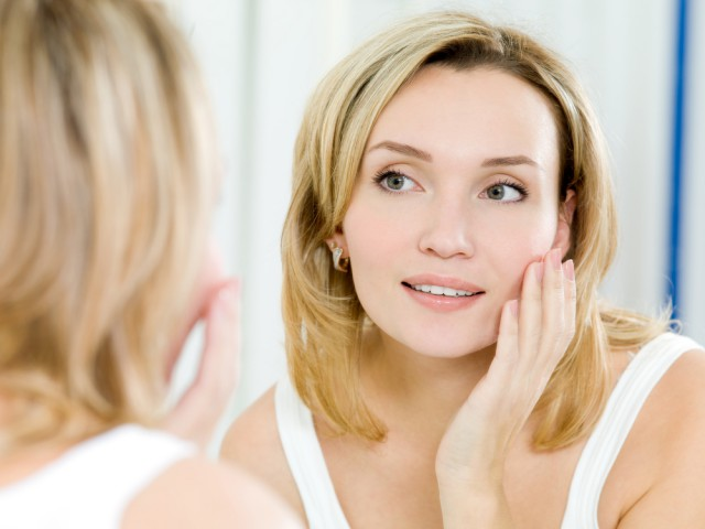 woman looking at complexion in mirror