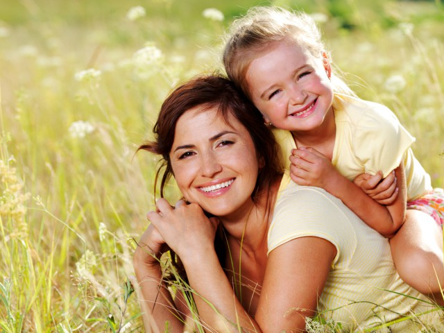 mom and daughter smiling outside