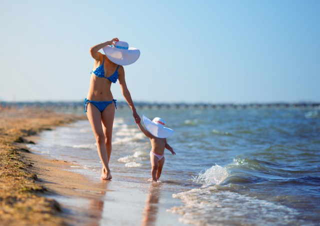 mom and baby in hats walking along beach