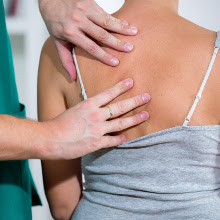 doctor examining female patient's back