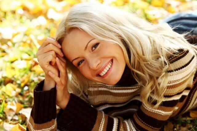 woman smiling in autumn leaves