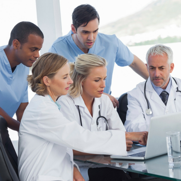 group of doctors looking at laptop