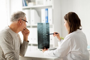 doctor and patient examining x-ray films