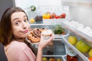 Woman with sweet food near refrigerator