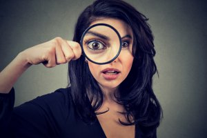Surprised woman looking through magnifying glass