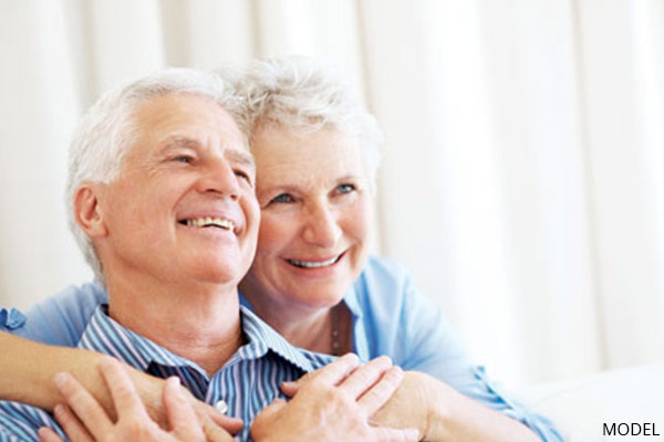 smiling older couple on couch