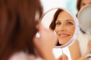 mature woman smiling looking in mirror